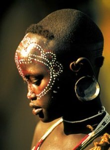 In contrast to the linear boldness of much surma body painting, some designs are delicate and lacy. Created to complement a young girl's fragile beauty, these designs are often set off by subtle patterns shaved into the hair.